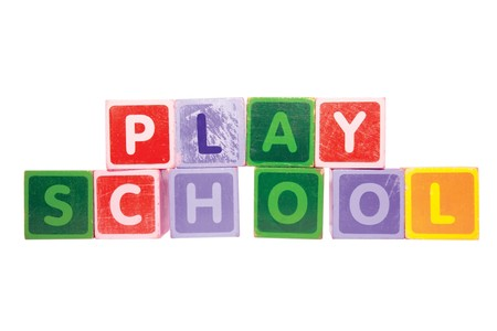 assorted childrens toy letter building blocks against a white background that spell playschool  photo