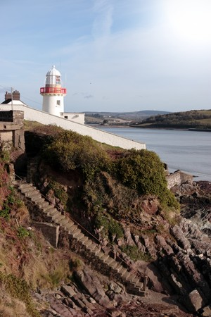 youghal: lighthouse during a sunny day on the rocks in with steps to beach in youghal county cork ireland