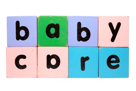 assorted childrens toy letter building blocks against a white background that spell baby care  photo