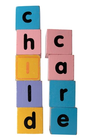 assorted childrens toy letter building blocks against a white background that spell childcare  photo