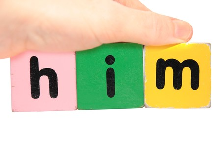 hand holding letter building blocks against a white background that spell him photo