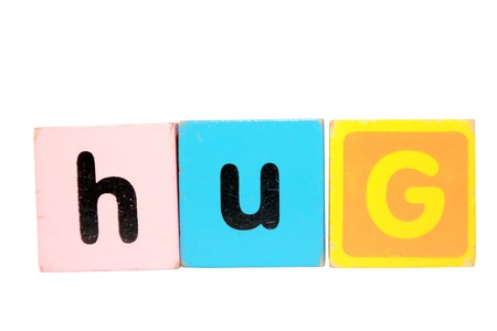 assorted childrens toy letter building blocks against a white background that spell hug  photo