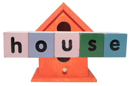 toy letters that spell house against a birdhouse   photo
