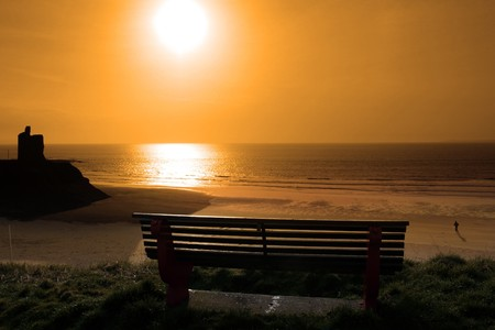 ballybunion bench in winter with view of beach castle and cliffs as the sun sets and a man jogging photo