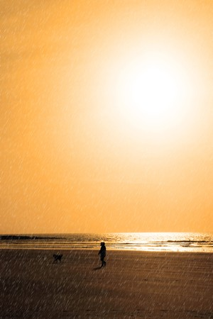 sunshine reflected on a golden beach during a rain storm with child and dog walking photo