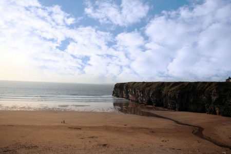 co  kerry: a view of the beach cliffs in ballybunion co kerry ireland with walkers