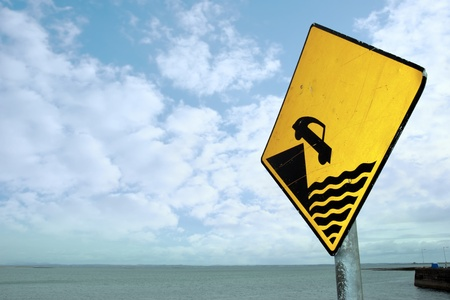 warning sign for drivers to be careful near the waters edge Stock Photo