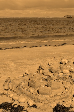 a sandcastle made with stones and sand on an irish shore with seaweed in sepia photo