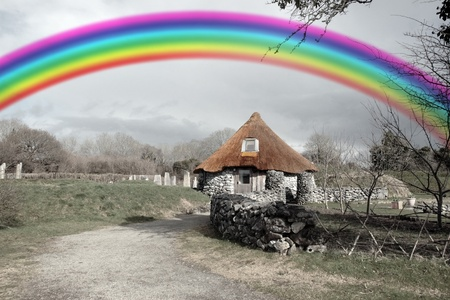 celts: historic ancient rustic cottage dwelling  in rural setting in ireland with rainbow in background Stock Photo