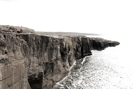 lone person on the cliffs edge on a rocky landscape of the burren in county clare ireland