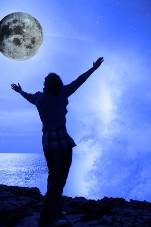 a lone woman raising her arms in awe at the powerful wave and full moon on the cliffs edge in county clare ireland