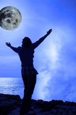 the universe: una mujer solitaria levantar sus brazos en pavor a la ola poderosa y Luna llena en el borde de los acantilados en el condado de clare Irlanda