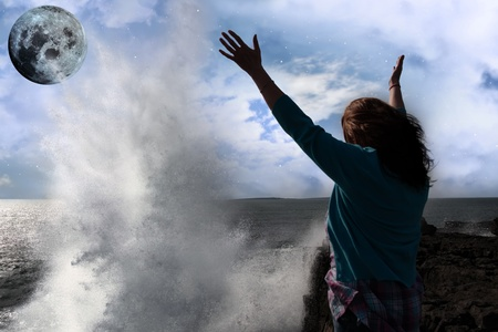 a lone woman raising her arms in awe at the powerful wave and full moon on the cliffs edge in county clare ireland Stock Photo - 8904448