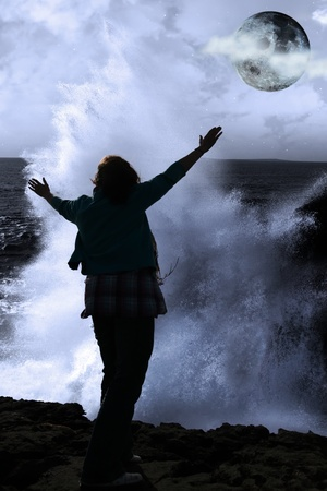 awe: a lone woman raising her arms in awe at the powerful wave and full moon on the cliffs edge in county clare ireland