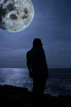 sadly: una donna solitaria guardando tristemente oltre il bordo di scogliere sotto la luna piena in Irlanda county clare