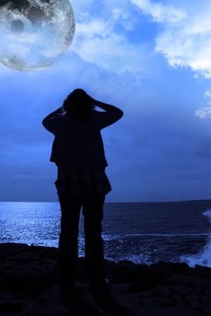 mujer mirando el horizonte: una mujer solitaria buscando tristemente sobre el borde de los acantilados bajo la luna llena en el condado de clare Irlanda Foto de archivo