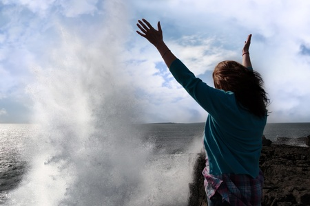 a lone woman raising her arms in awe at the powerful waves on the cliffs edge in county clare ireland