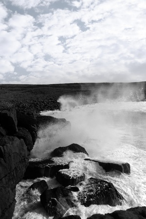 cliffs and coastline of the burren in county clare ireland with giant waves crashing on the rocks in black and white photo