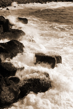 burren: cliffs and coastline of the burren in county clare ireland with giant waves crashing on the rocks in sepia