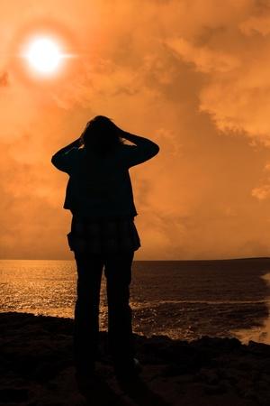 mujer mirando el horizonte: una mujer solitaria buscando tristemente sobre el borde de los acantilados en el condado de clare Irlanda