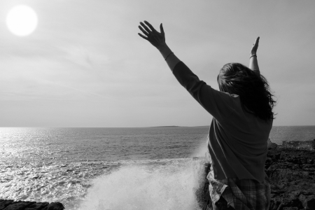 a lone woman raising her arms in awe at the powerful waves on the cliffs edge in county clare ireland in black and white Banco de Imagens