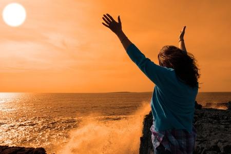 gratitudine: una donna solitaria, alzando le braccia in soggezione alle potenti onde sul bordo scogliere nella Contea di clare Irlanda nel sole splendente