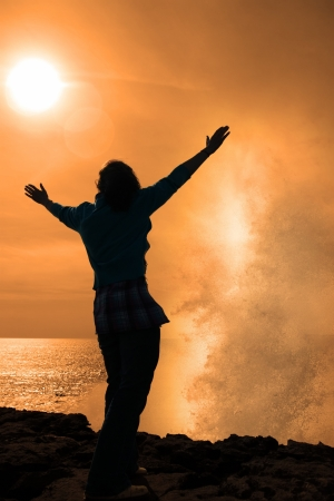 a lone woman raising her arms in awe at the powerful waves on the cliffs edge in county clare ireland in glorious sunshine