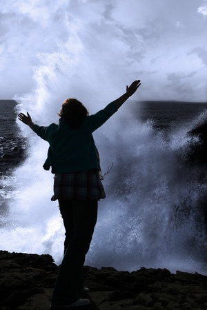 a lone woman raising her arms in awe at the powerful waves on the cliffs edge in county clare ireland photo