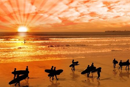 Surfers marcher sur la plage en Irlande de comté de clare lahinch comme le soleil descend