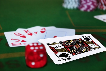 green casino table with dice and a hand of a royal flush in a poker game and the jack of spades in the pack