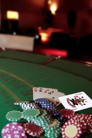 green casino table with chips and four aces in a poker game and a joker in the pack