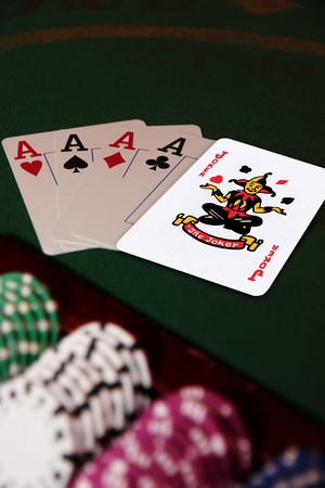 green casino table with chips and four aces in a poker game and a joker in the pack Stock Photo - 9281385