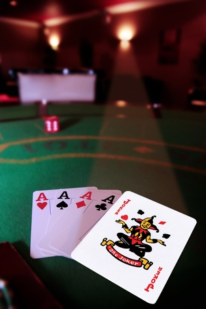 green casino table four aces in a poker game and a joker in the spotlight Stock Photo - 9327034