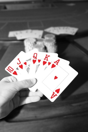casino table with a hand of a royal flush in a poker game in black and white photo