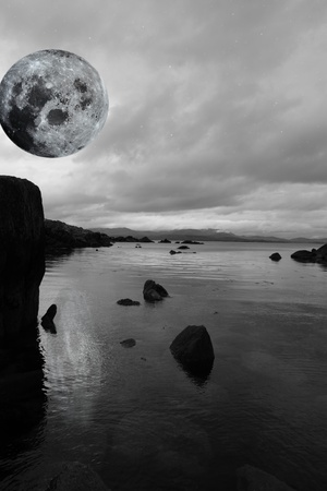 black and white night scenic view in kerry ireland of rocks and sea with mountains against a beautiful blue cloudy sky photo