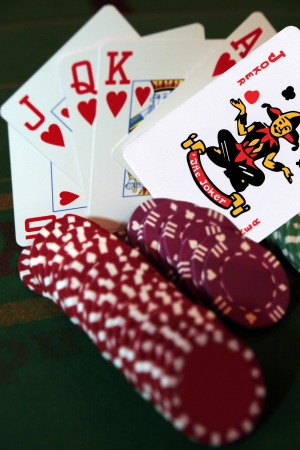 green casino table with chips and a hand of a royal flush in a poker game and a joker in the pack