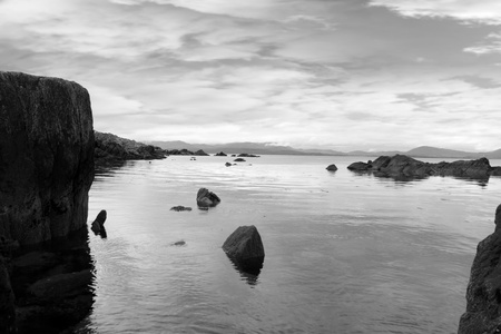 black and white scenic view in kerry ireland of rocks and sea with mountains against a beautiful blue cloudy sky Stock Photo - 10367309