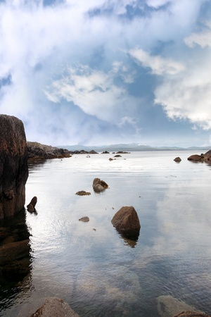 scenic view in kerry ireland of rocks and sea with mountains against a beautiful blue cloudy sky Stock Photo - 10367316