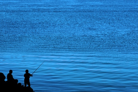 a silhouette of a father and son fishing of the rocks in ireland photo