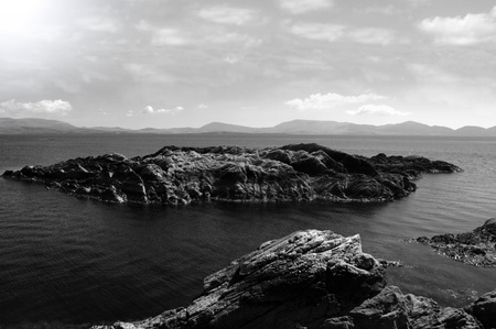 scenic view in kerry ireland of rocks and sea with mountains against a beautiful cloudy sky in black and white Stock Photo - 10445287