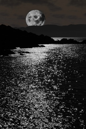 scenic view in kerry ireland of rocks and sea with a moon rising behind mountains against a night sky Stock Photo - 10445295