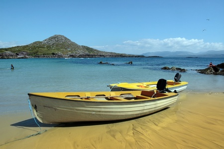 yellow boats: yellow boats moored at a sandy beach on the coast of county kerry ireland