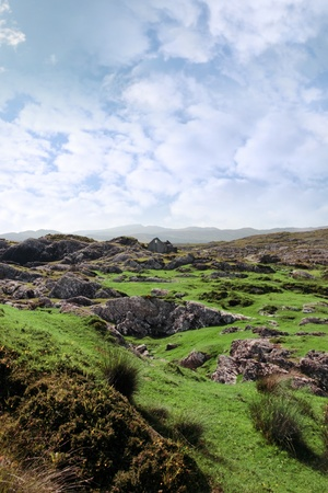 scenic view of abandoned house in rugged rocky green irish landscape photo