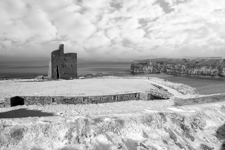 a seasonal snow covered view of atlantic ocean and ballybunion castle beach and cliffs on a frosty snow covered winters day in black and white