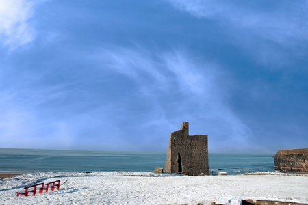 a seasonal snow covered view of atlantic ocean and ballybunion castle with red benches on a frosty snow covered winters day photo