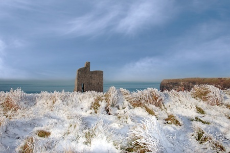 a seasonal snow covered view of atlantic ocean and ballybunion castle and cliffs on a frosty snow covered winters day