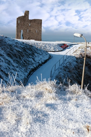 a seasonal snow covered view of atlantic ocean and ballybunion castle on a frosty snow covered winters day