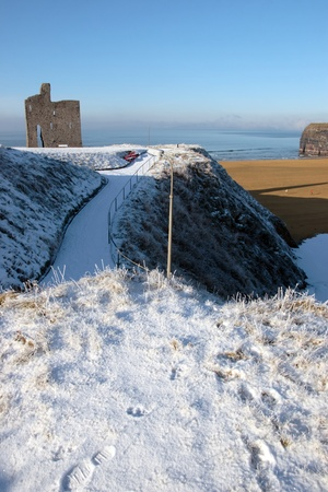a seasonal snow covered view of atlantic ocean and ballybunion castle beach and cliffs on a frosty snow covered winters day photo