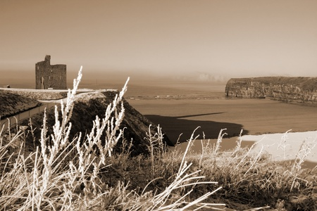 a seasonal snow covered view of atlantic ocean and ballybunion castle beach and cliffs on a frosty snow covered winters day in sepia photo