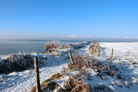 a seasonal snow frosty covered slippery cliff walk with a blue cloudy sky background photo